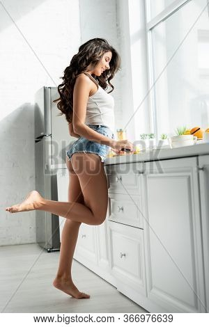 Side View Of Smiling Girl In Denim Shorts Cutting Lemon On Worktop In Kitchen