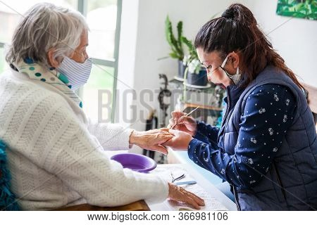 Senior Woman Getting A Manicure At Home During Covid-19 Pandemic Wearing Face Mask