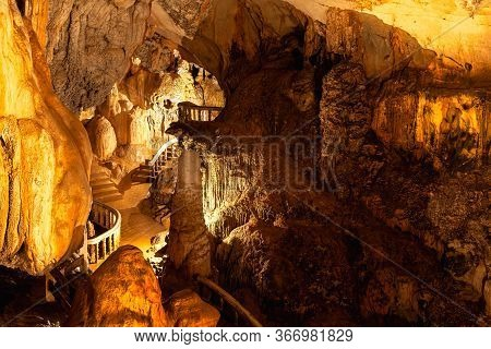 Stalactites In Limestone Cave Adorned With Light