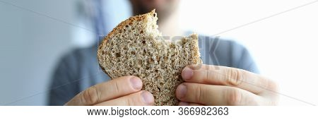 Man Shows Bitten Wholemeal Healthy Homemade Bread. Threat Hunger During Global Pandemic. Saving Prod