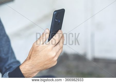 Man Holds The Phone In His Hand