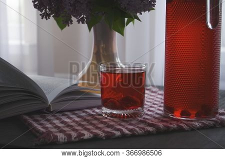 Still Life With A Bouquet Of Lilacs And Compote Of Berries. A Glass Of Compote, A Jug, A Bouquet, A