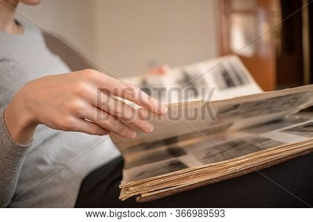 Girl In A Gray Jacket Holds An Old Photo Album With Black And White Photos On Her Lap And Looks At T