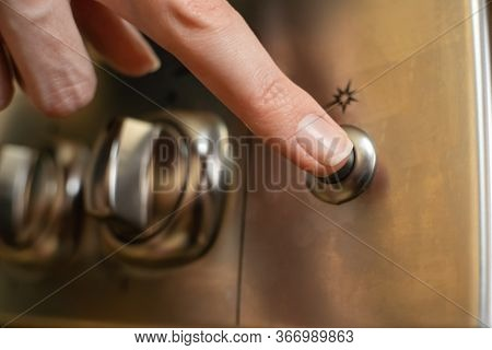 Woman's Hand Presses The Electric Ignition Button On A Stainless Steel Gas Stove Close Up
