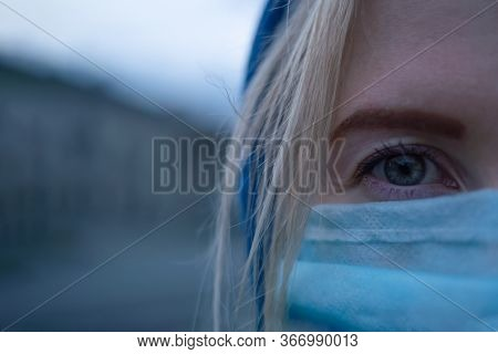 Half Of The Face Of A Young Blonde Woman With A Stole On Her Head In A Medical Mask Close-up On One
