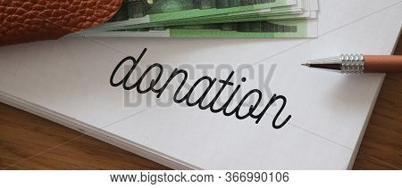 Word Writing Text Donation On Page Of Copybook. With Some 100 Euro Bills On It. Business Concept For