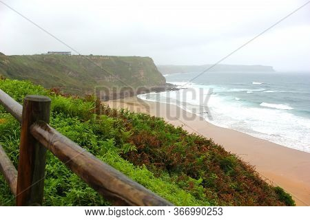 View Of The Sandy Beach In Cloudy Foggy Day. Spain, Suburb Of Suances, Rainy Day In The Province Of