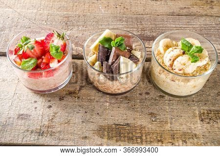 Set Various Fruit Overnight Oatmeal. Oats Porridge With Strawberry, Bananas, Chocolate, Nuts In Smal