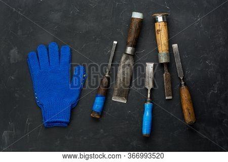 Carpenter Tools And Working Gloves On Dark Background. Minimal Black.