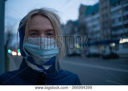 Young Blonde Woman With A Stole On Her Head In A Medical Mask Close-up On A Street In The City. Prev