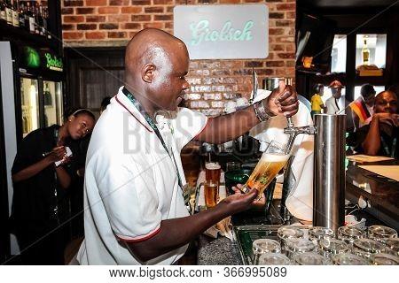African Barman Pouring A Pint Draft Beer At Barman Training School