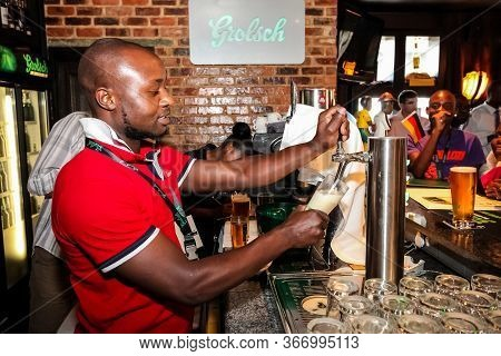 Johannesburg, South Africa - November 8, 2011: African Barman Pouring A Pint Draft Beer At Barman Tr