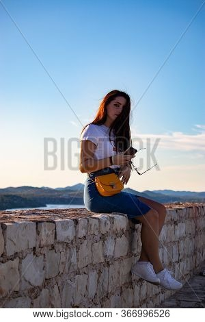 Attractive Brunette Sitting On A Wall Of Sibenik Fortress, Looking Dramaticaly At The Camera, Wind B