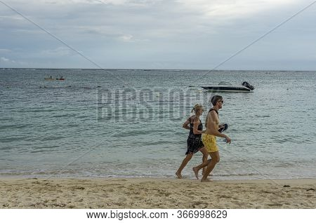 Mauritius, January 2020 - Couple Strolling At The Beach And Smiling, Enjoying Summer Holidays On A T