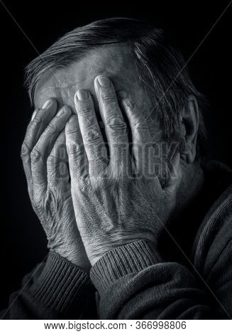 Elderly man covered his face with his hands