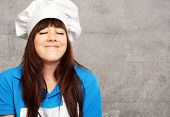 portrait of a young female chef satisfied, indoor poster