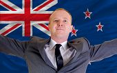 joyful investor spreading arms after good business investment in new zealand in front of flag poster