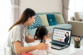 Asian Kindergarten School Girl With Mother Video Conference E-learning With Teacher On Laptop In Liv