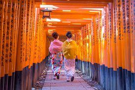 Kyoto, Japan - December 13, 2014: Two Geishas Walking Through Orange Gates Called Torii At The Fushi