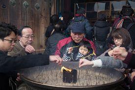 Nara, Japan - December 28, 2014: Devotees Lightening Incense Sticks At Todai-ji Temple