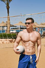 Handsome Fit Strong Athletic Young Man In Swimming Trunks Holds A Volleyball Ball On A Beach Sand Vo