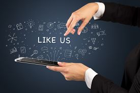 Close-up of a touchscreen with LIKE US inscription, social media concept