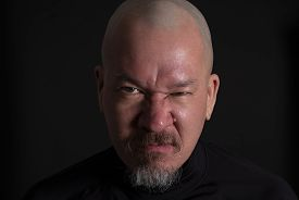 A Bald Man With Beard And An Angry Expression On His Face On Black Background