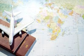 Passport With A Map Background.travel Planning.top View Of Traveler Accessories With A Plane  On Wor
