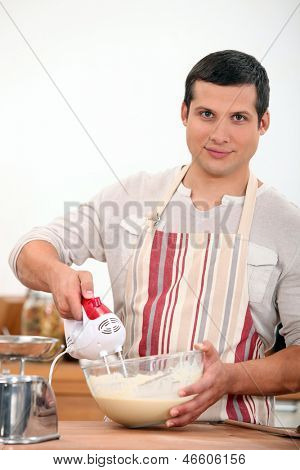 young man using an electric egg beater