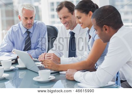 Business people looking at a laptop during a meeting
