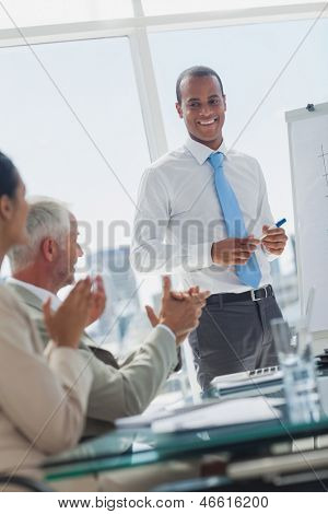 Manager is being applauded by colleagues at the end of a presentation