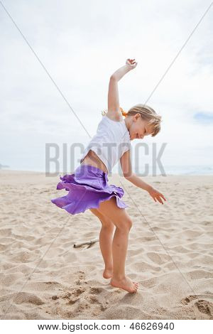 Young Girl Jumping In Sand