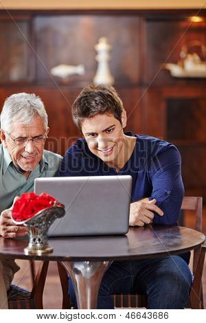 Senior and young man looking at laptop computer in a caf���©