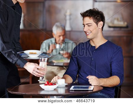 Waiter bringing man a cocktail in a hotel