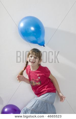 Little happy giggle girl playing with colour balloons. Girl celebrates her birthday. Her hairs electrified poster