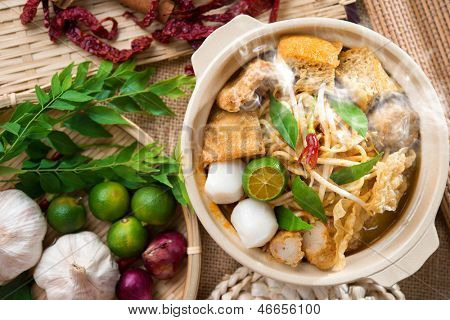 Hot and spicy Singaporean Curry Noodle or laksa  mee with hot steam in clay pot, decoration setup, serve with chopsticks. Singapore cuisine.