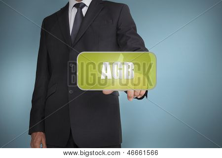 Businessman touching green tag with the word agb written on it on blue background