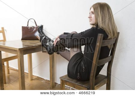 Young Blond Woman In Black Dress Sitting On Chair