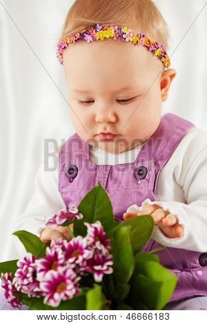 Portrait of little girl dressed in violet pinafore dress with headband in form of chaplet on her head with bunch 0f flowers
