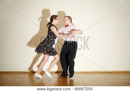 Young happy man and woman in dress dance at boogie-woogie party.