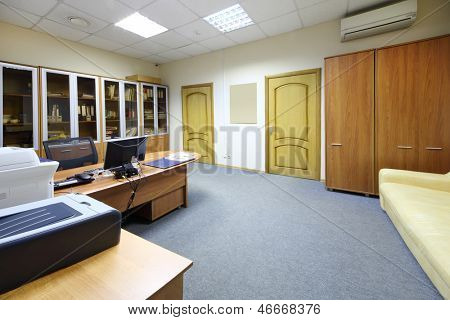 Empty working area with desktop, bookcase and sofa in modern office.