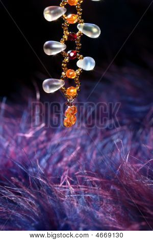 Orange stone jewel necklace over blue purple feather background poster