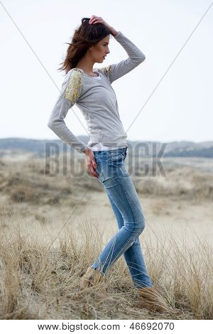 Beautiful Woman Wearing Grey Shirt And Jeans In The Dunes