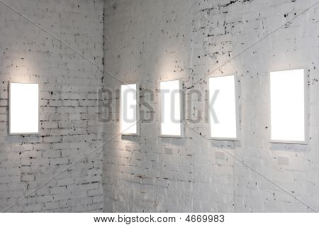 poster of Five white empty frames on exposition on wall