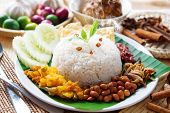 Nasi lemak traditional malaysian hot and spicy rice dish, fresh cooked with hot steam. Served with belacan, ikan bilis, acar, peanuts and cucumber. Decoration setup. poster