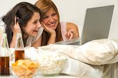 Teenagers friends enjoy movie night watching laptop and laughing poster