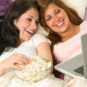 Pretty sisters lying on bed watching funny movie poster