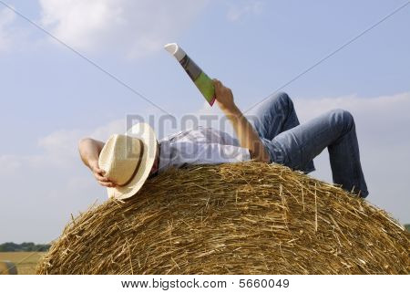 Young man lying on a straw bale reading a magazine
