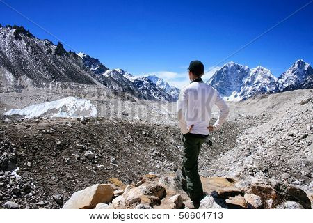 Rear View of Hiker in standing the Khumbu Valley with the Himalayan Mountain Range in background near Gorak Shep in the Sagarmatha (Mount Everest) National Park in Nepal poster