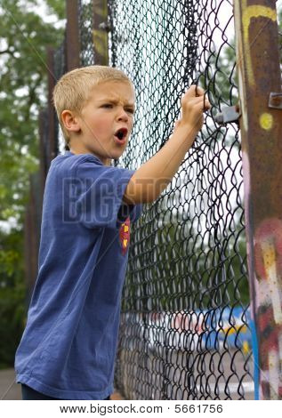 An angry young boy shouting through a chain link fence poster